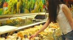 Woman with shopping cart coming up to the fridge and taking product from it. Stock Footage