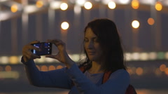 The girl with the phone looks at the bridge of Perth, the great, Neva river Stock Footage