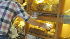 Man chooses and putting a fresh bread loaf into a package in the supermarket Stock Footage