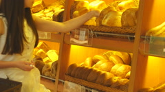 Woman chooses and putting a fresh bread loaf into a package in the supermarket. - stock footage