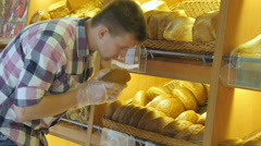 Man chooses a fresh bread loaf in the supermarket. Shopping in the grocery - stock footage