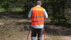 Hiker with walking sticks on the forest road in summer Stock Footage