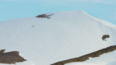 Aerial view of people climbing a snow covered mountain in Alaska USA Stock Footage