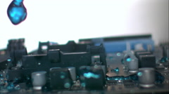Dynamic sweep across circuit board as blue liquid floods through. Slow motion. Stock Footage