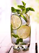 On wooden boards is glass with mohito and lime. - stock photo