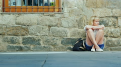 Tired woman sitting on the street. Passing by people. Concept - get lost in an Stock Footage