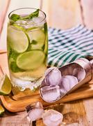 On wooden boards is glass with mohito and scoop ice. - stock photo