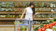 Young woman pushing cart along the grocery and buying mushrooms at store Stock Footage