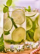 On wooden boards is glasses with mohito and lime. - stock photo