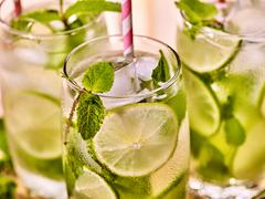 On wooden boards glasses with mohito and scoop ice. - stock photo