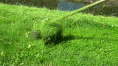 Сuts the grass with a lawnmower. Stock Footage