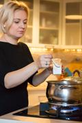 Housewife cooking meal on gas stove adding ingredients to boiling pan - stock photo