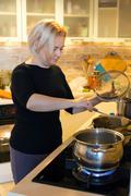 Housewife cooking meal on gas stove adding ingredients to boiling pan Stock Photos
