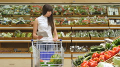 Woman pushing cart along the grocery aisles and using tablet pc Stock Footage