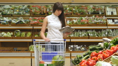 Young woman pushing cart along the grocery aisles in the supermarket. - stock footage