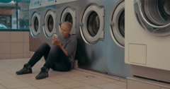 Woman with mobile waiting for the laundry Stock Footage