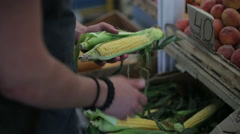 Man buys corn at a vegetable market in the day Stock Footage