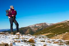 Energetic Female Hiker Staying on Snowy Terrain and Observing Scenic Mountain Stock Photos