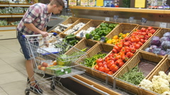 Man pushing cart along the grocery aisles in supermarket and choosing vegetables Stock Footage