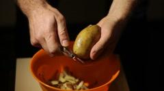 Closeup view of a male hand peeling an organic potato Stock Footage
