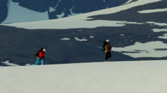 Aerial view male female climbers on snow covered mountains in Alaska Stock Footage