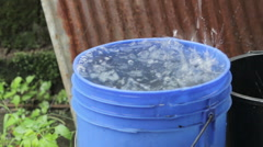 Blue bucket holds runoff from a roof during a rainstorm Stock Footage