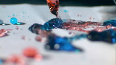 Streams of red, green and blue liquid splash onto white surface. Slow motion ECU Stock Footage
