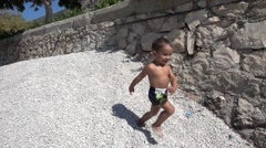 Slow motion small child runs down a pile of pebbles.mp4 Stock Footage