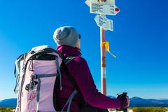 Hiker with Backpack Staying and Looking on Trail Sign Stock Photos