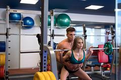At gym. Instructor helps girl to do squat - stock photo