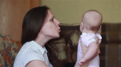 Happy mother holds a baby on hands and talking Stock Footage
