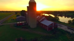 Summer sunrise revealed from behind silo with tranquil river Stock Footage