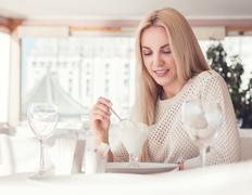 Young woman in sunny restaurant with ice-cream desert - stock photo