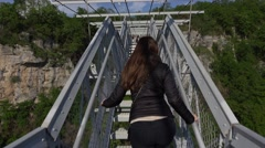 Girl go upstairs, hold on banister and turn head, narrow footbridge to rock Stock Footage