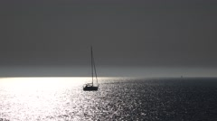Lonely yacht sail away at sunset, glittering sea water at sunset Stock Footage