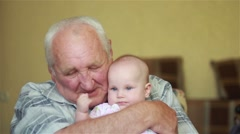 Happy grandfather holds a baby on hands and talking Stock Footage