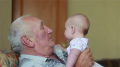 Happy grandfather holds a baby on hands and kissing Stock Footage