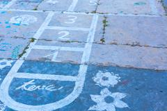 Hopscotch on an asphalt floor with chalk drawings of numbers and squares Stock Photos