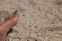 Female foot with cyan pedicure in beach sand Stock Photos