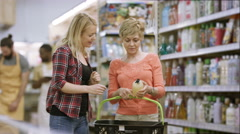 4K Mother & daughter shopping in frozen food aisle of supermarket Stock Footage