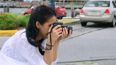 Girl taking pictures outside with her DSLR camera - stock footage