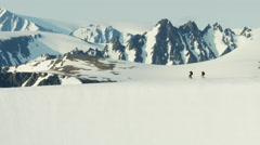 Aerial view of climbers crossing a snow covered mountain range in Alaska USA - stock footage