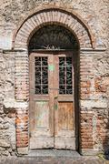 Old wooden door with brick archway. - stock photo