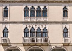 Decorated arched windows of a medieval palace. Stock Photos