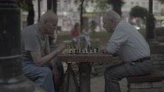 Two seniors elderly men playing chess in the Park Stock Footage