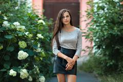 Young beautiful brunette woman in black leather skirt with clutch - stock photo
