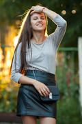 Young beautiful brunette woman in grey blouse black leather skirt and clutch - stock photo
