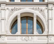 Semicircle white window  crossed by decorated columns. - stock photo