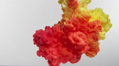 Yellow and Orange ink droplets mixing ISOLATED ON WHITE in slow motion. Stock Footage
