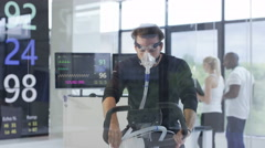 4K Man with breathing equipment on exercise bike testing fitness levels in gym Stock Footage